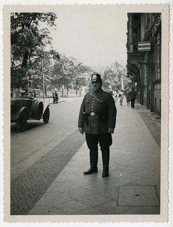 Large man in uniform with gun on city street