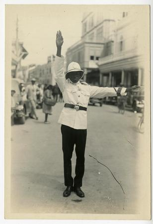 Man in uniform with white hat and shirt, directing traffic