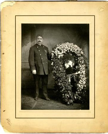 Richard Enright in NYPD Uniform in front of a large wreath